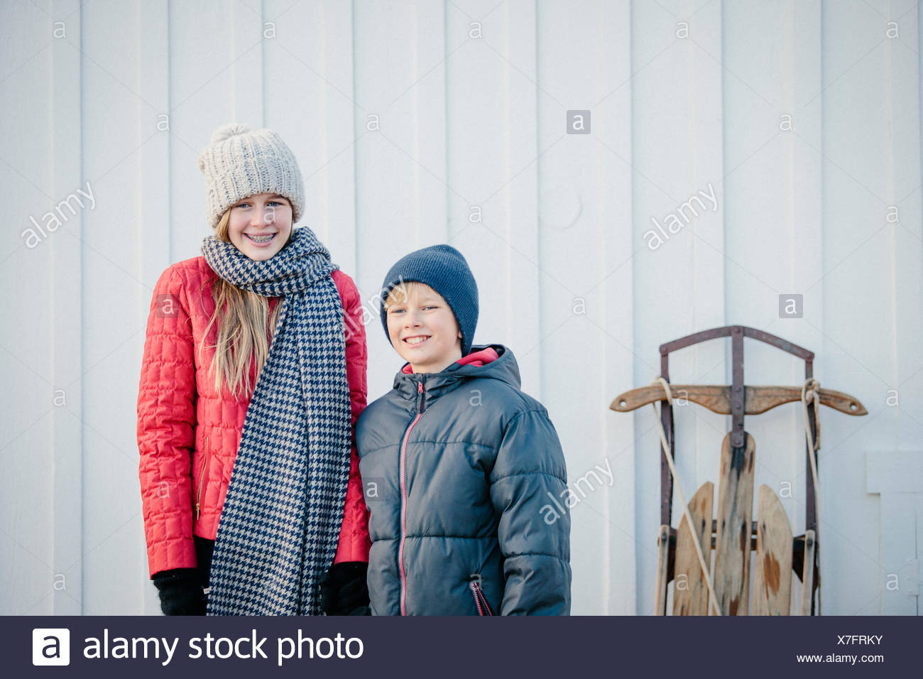 A brother and sister side by side in a yard in winter. - Stock Image