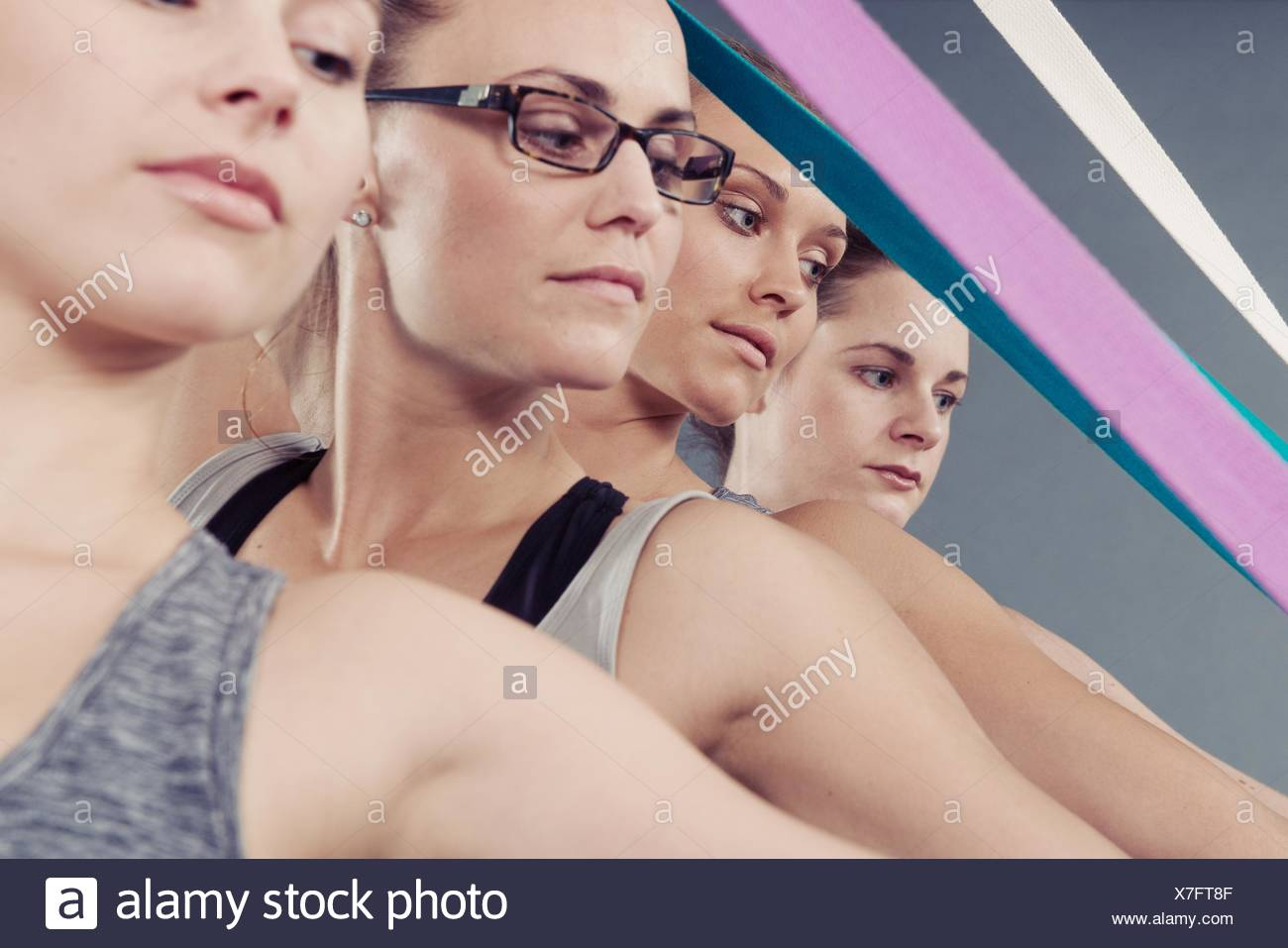 Young women using coloured bands, grey background - Stock Image