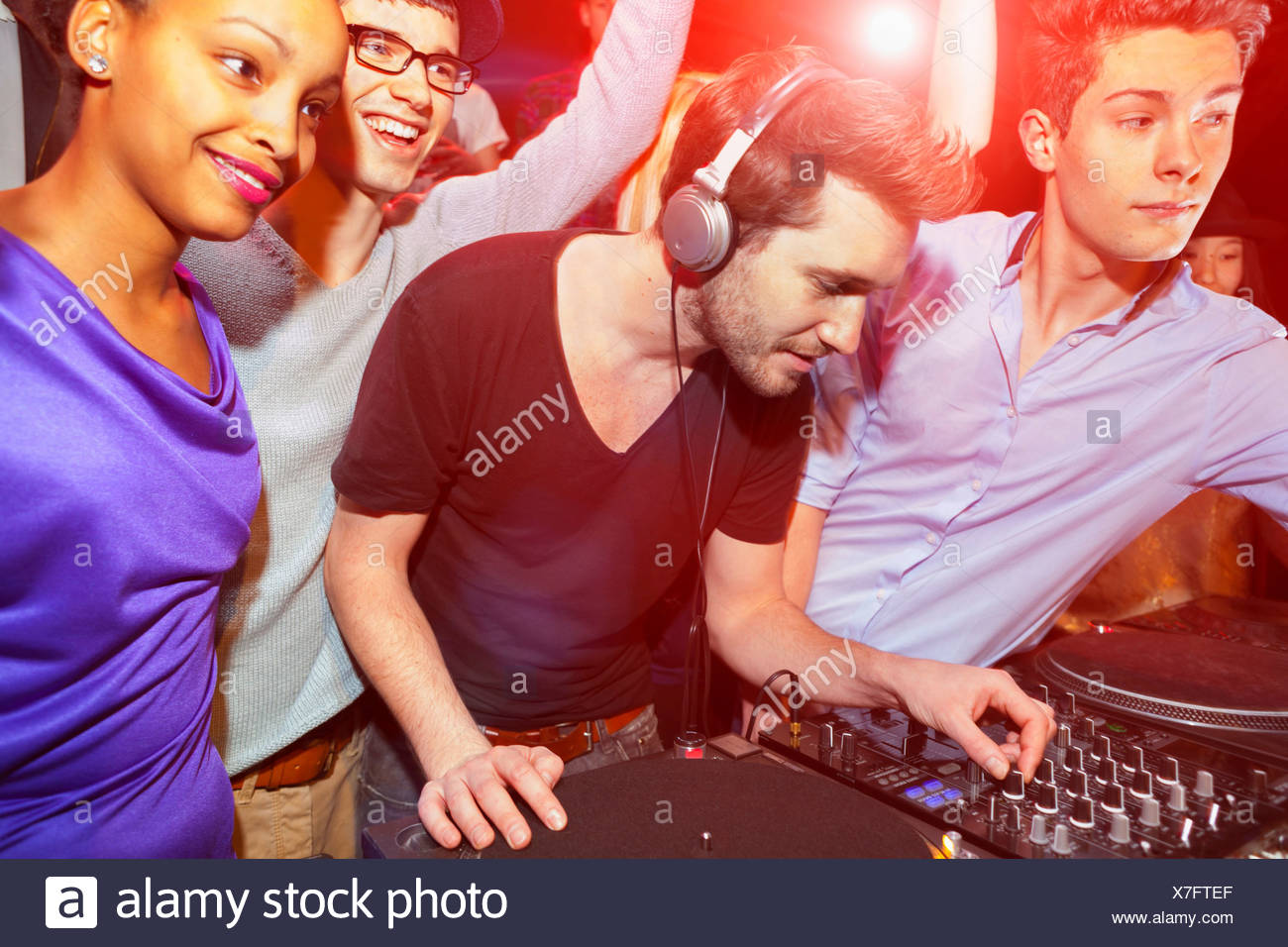 Disc jockey with group of people behind mixing desk - Stock Image