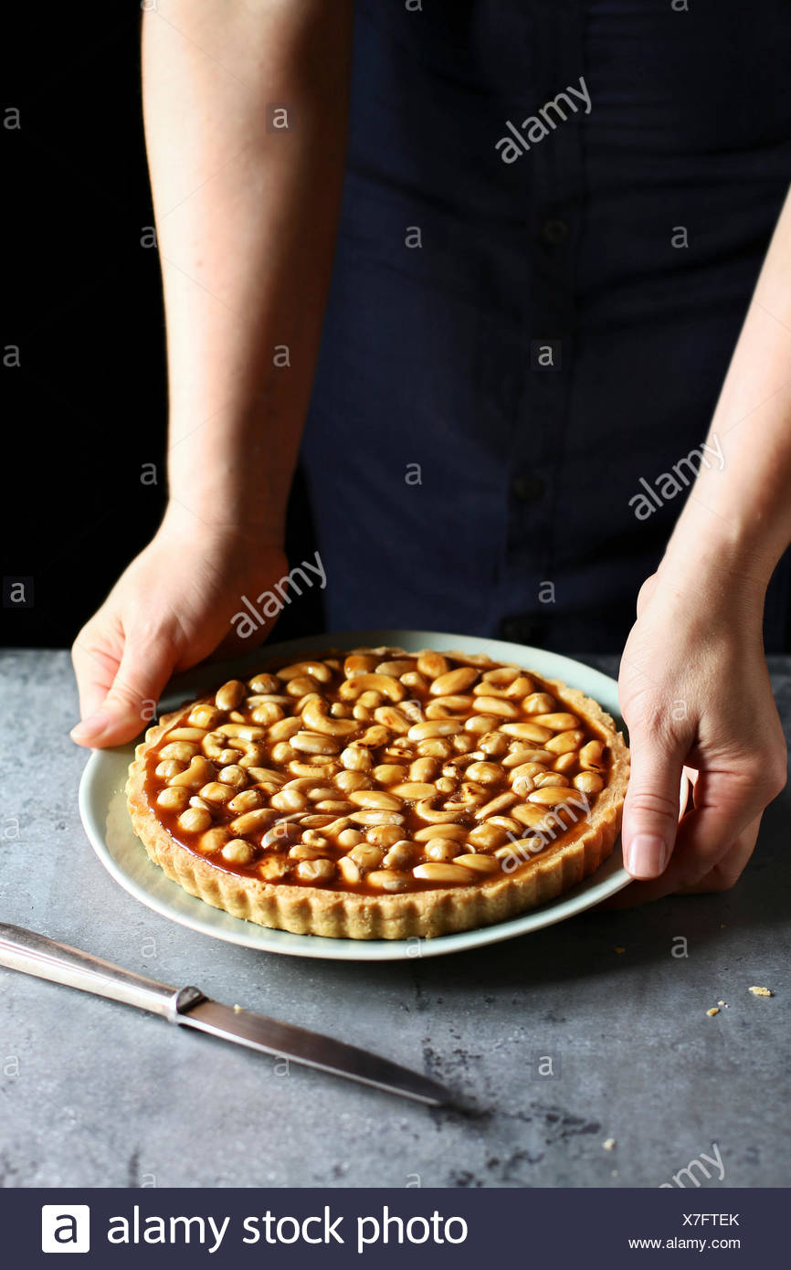 Female hands holding a caramel nut tart on a plate - Stock Image