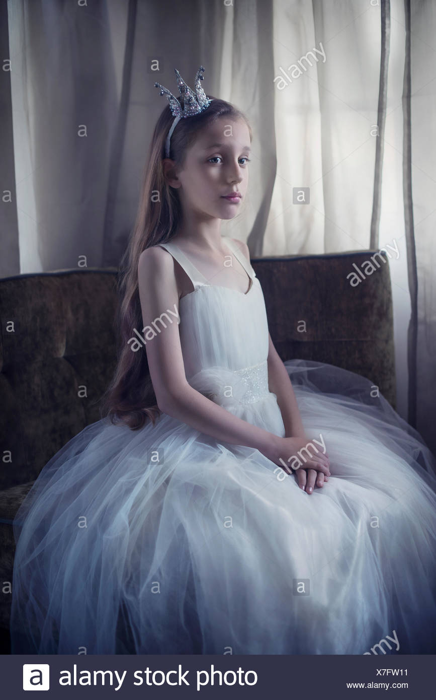 Portrait of a girl sitting on a chair dressed in a princess outfit - Stock Image