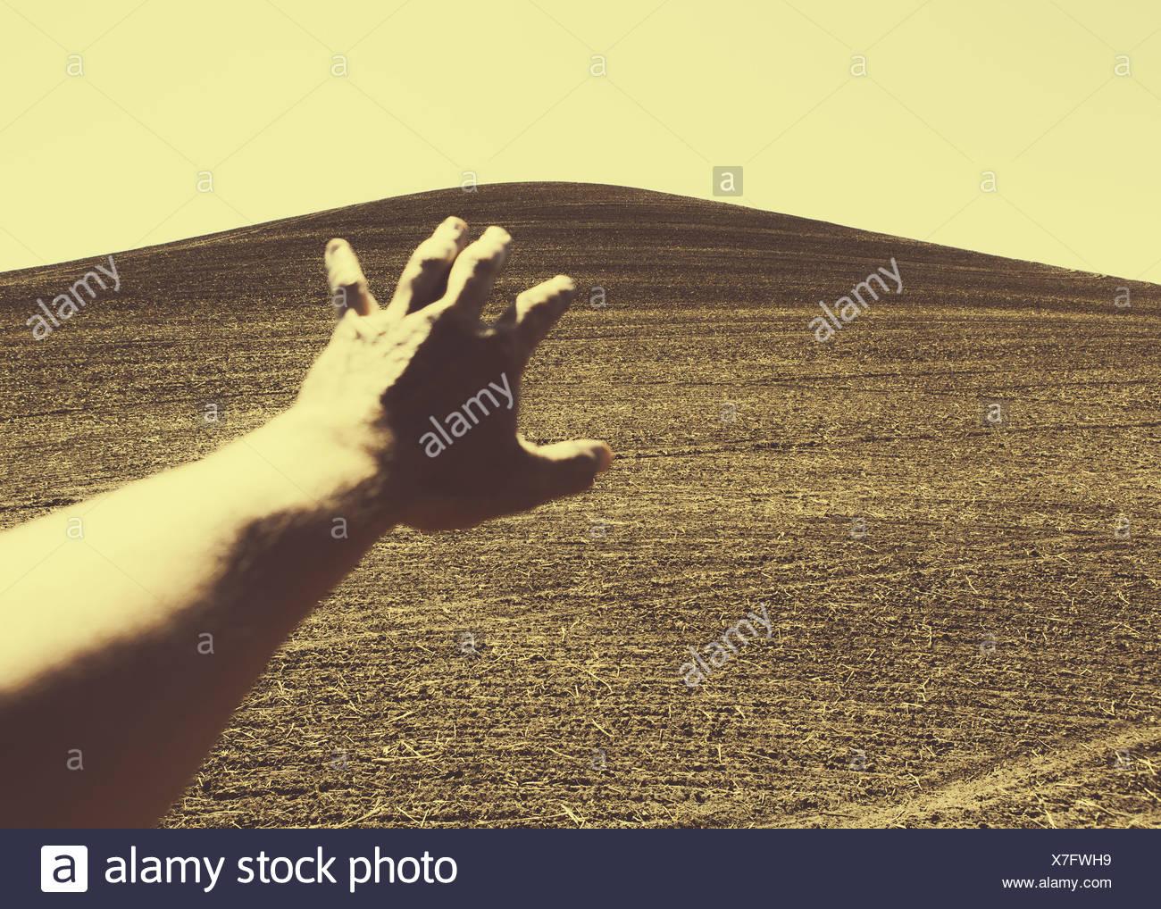 Hand extending towards ploughed farmland, near Pullman - Stock Image