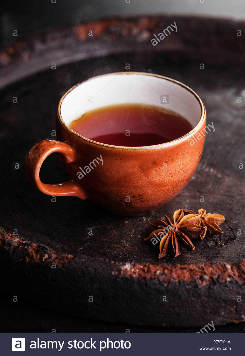Hot tea with spices on dark background - Stock Image