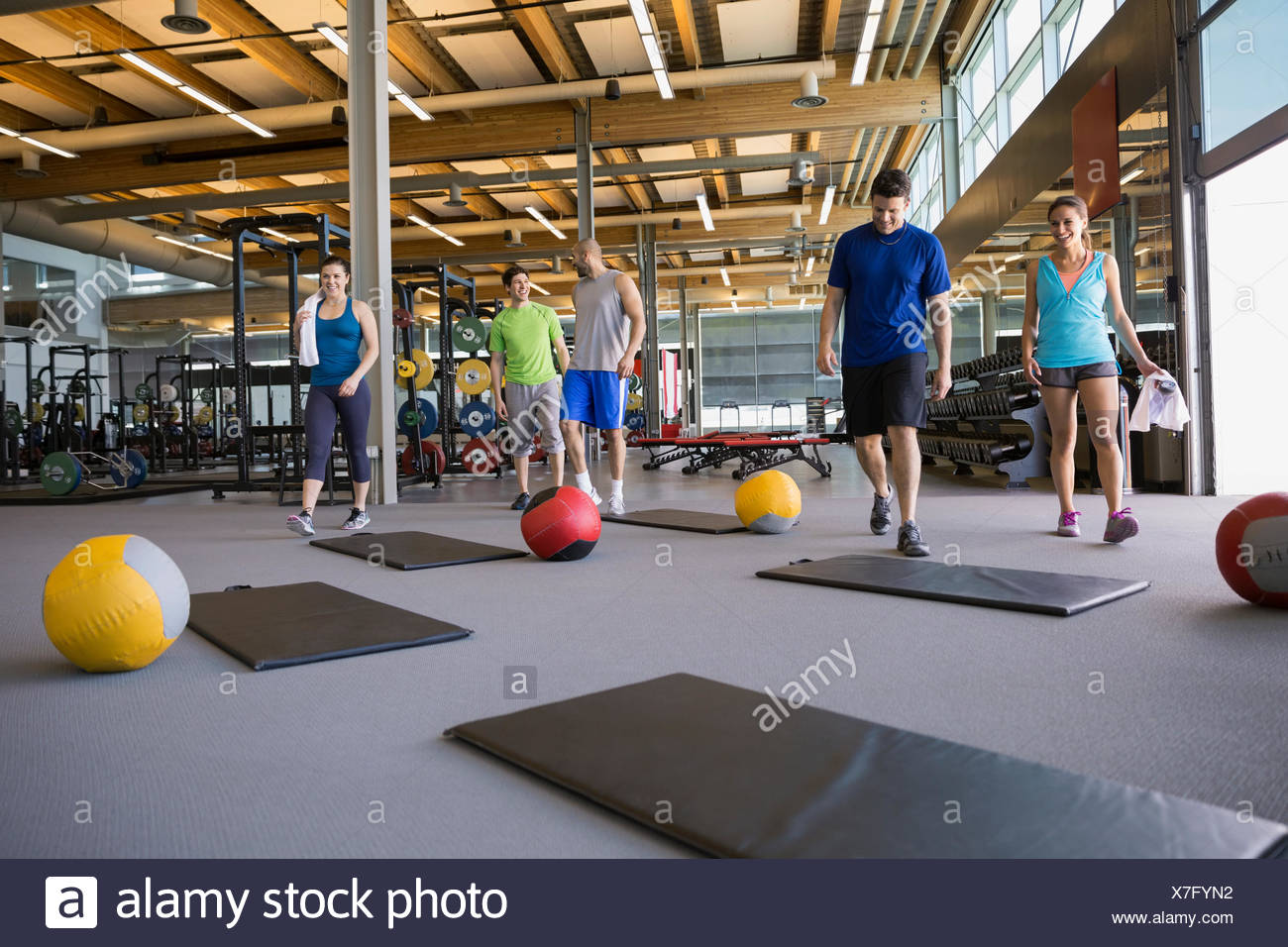 Exercise class approaching mats with medicine balls - Stock Image