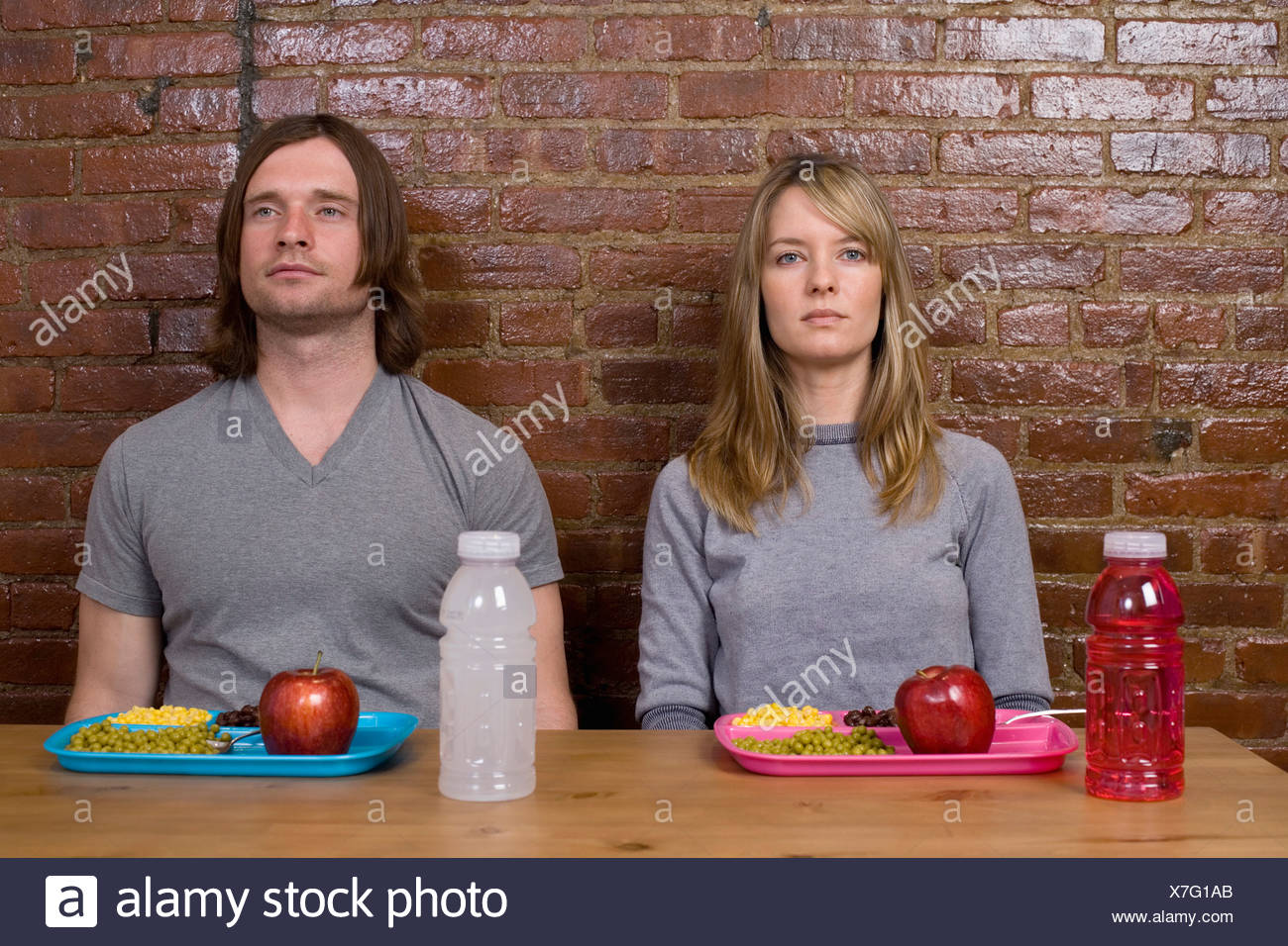 A young couple sitting at a table with sports drinks and plastic trays of food - Stock Image