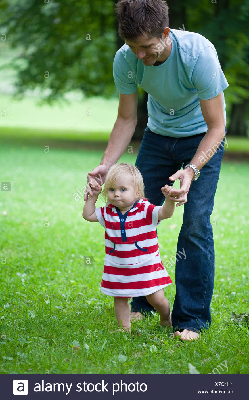 Mid adult father helping daughter with first steps - Stock Image
