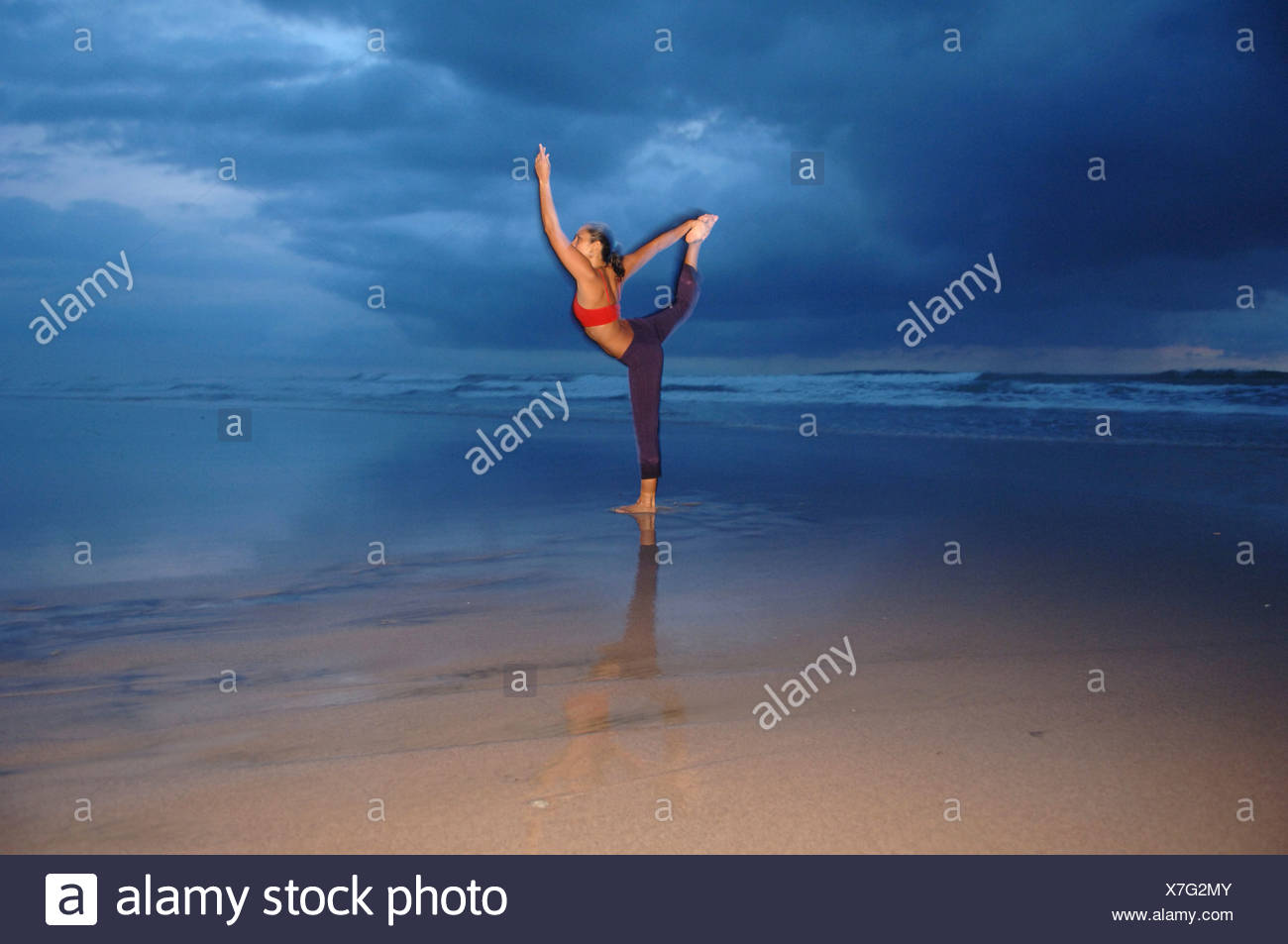 Female performs yoga on the beach - Stock Image
