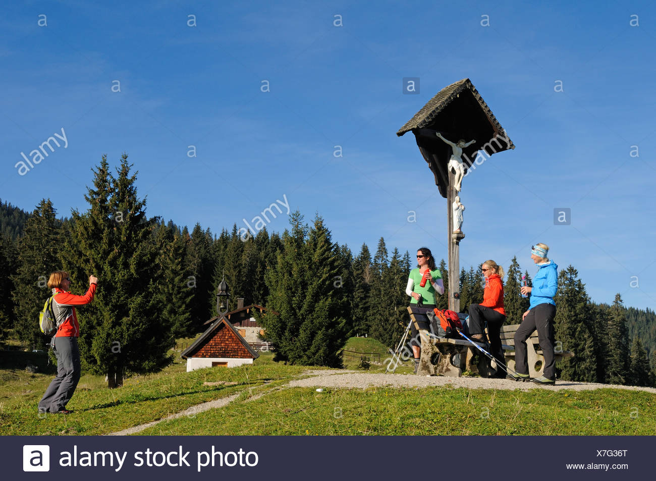 Female hikers having someone take a picture of them in front a cross on Winklmoosalm alp, Reit im Winkl, Chiemgau, Bavaria - Stock Image