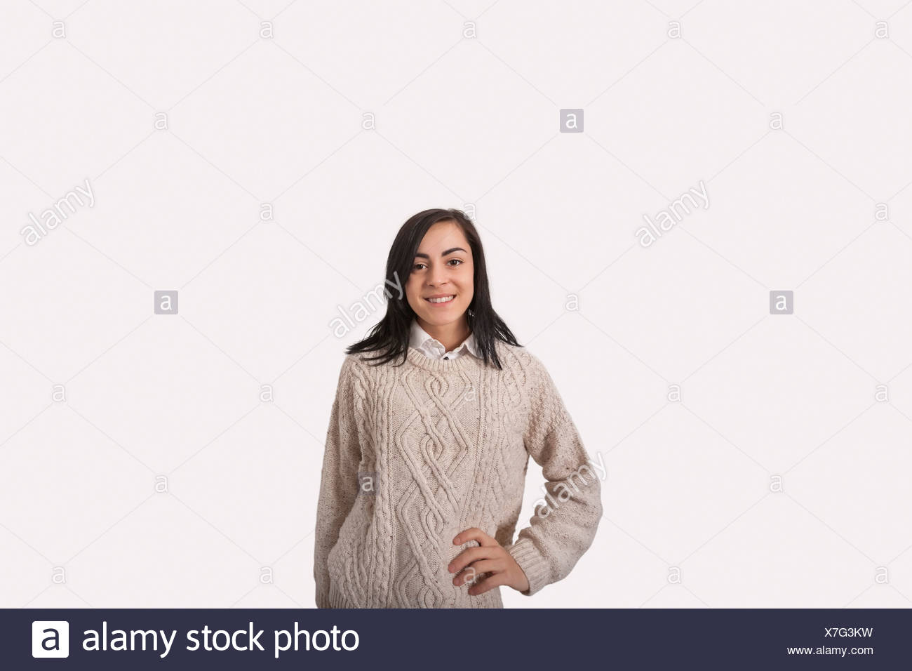Portrait of confident businesswoman with hand on hip standing against gray background - Stock Image