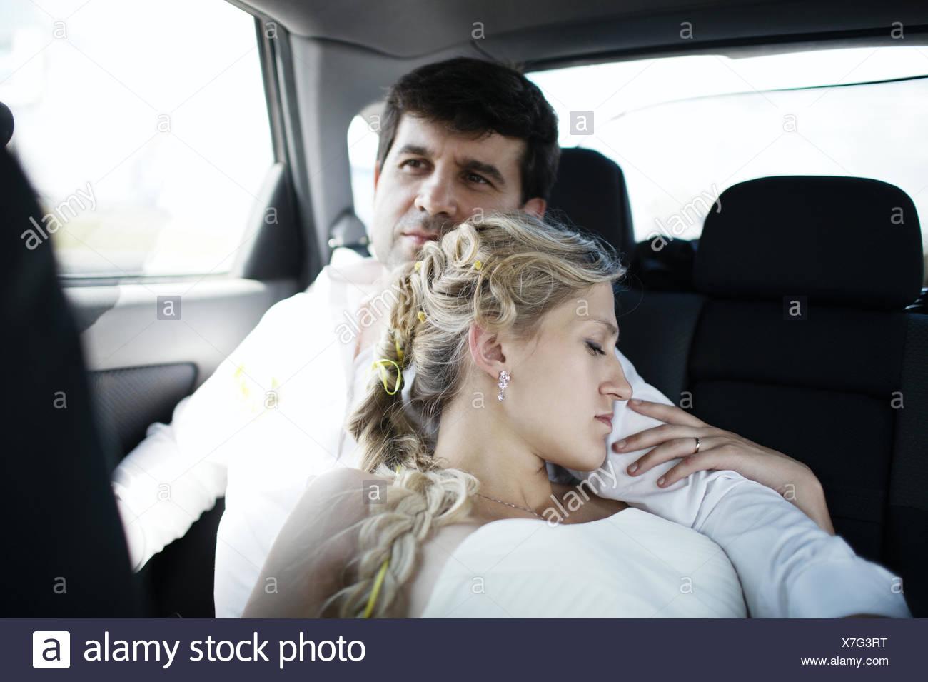Woman sleeping on her husbands shoulder - Stock Image