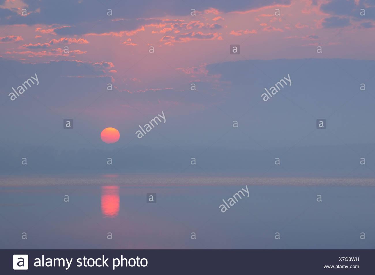 Germany, Mecklenburg-Vorpommern, Mecklenburger Seenplatte, Plau am See, View of sunrise with reflection in lake - Stock Image