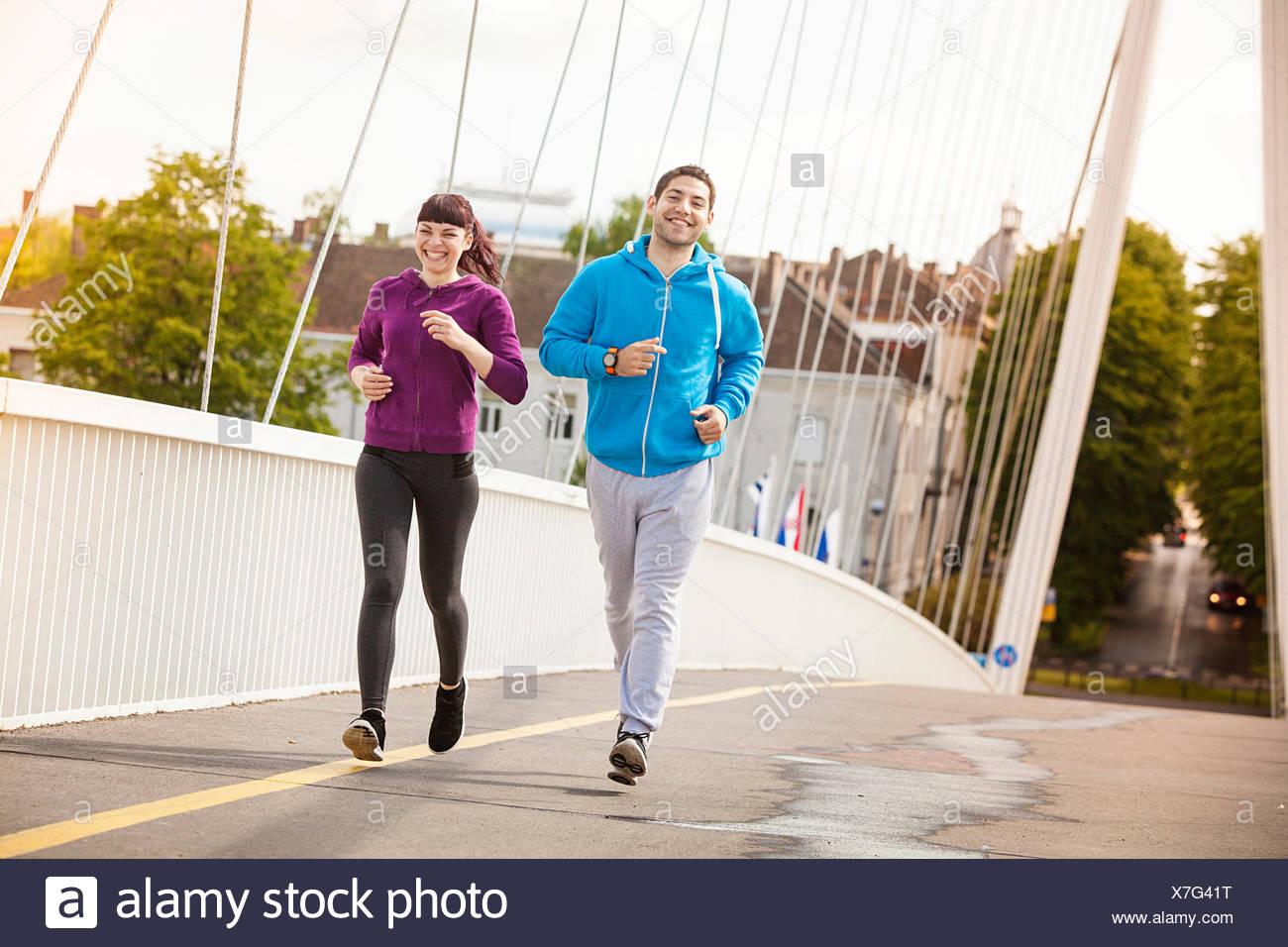 Young couple jogging on bridge, Osijek, Croatia - Stock Image