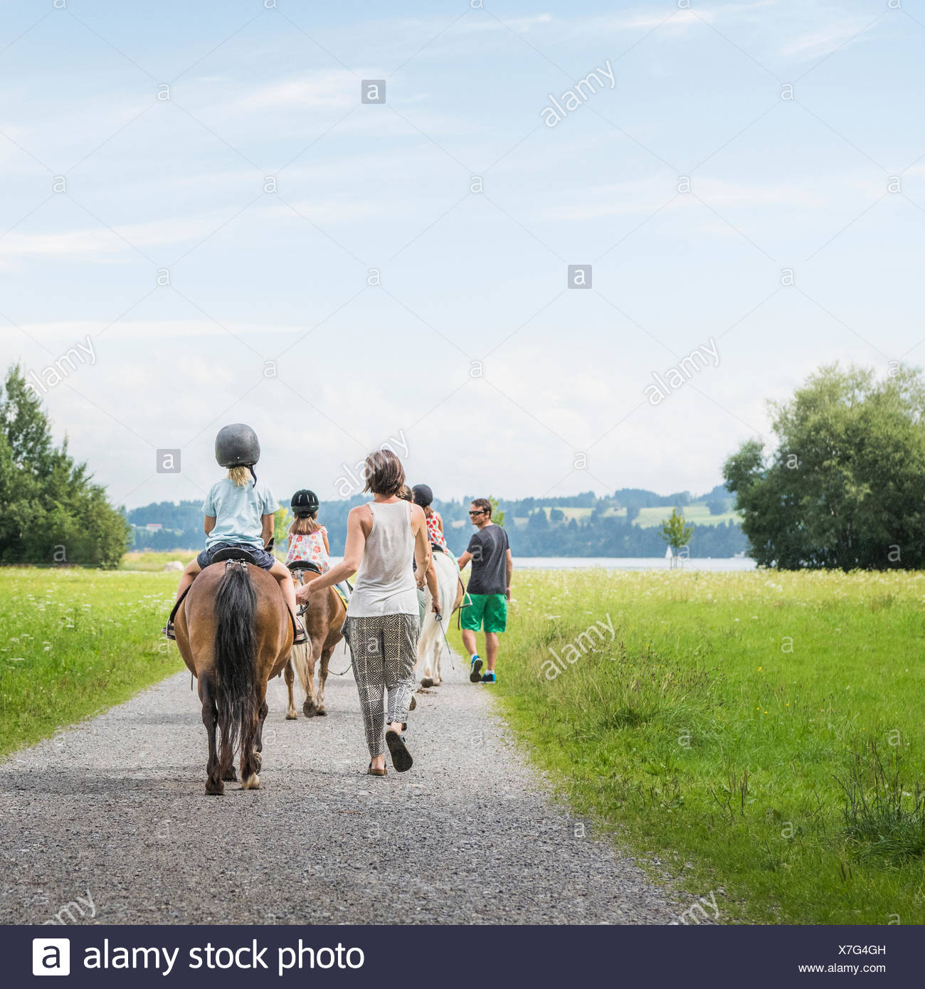 Rear view of parents guiding children on horse, Fuessen, Bavaria, Germany - Stock Image