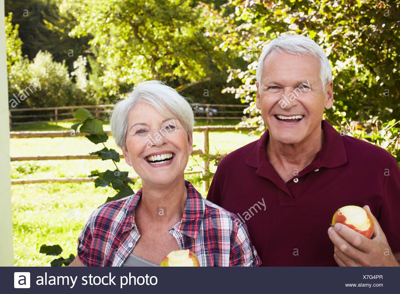 Senior couple eating apples smiling - Stock Image