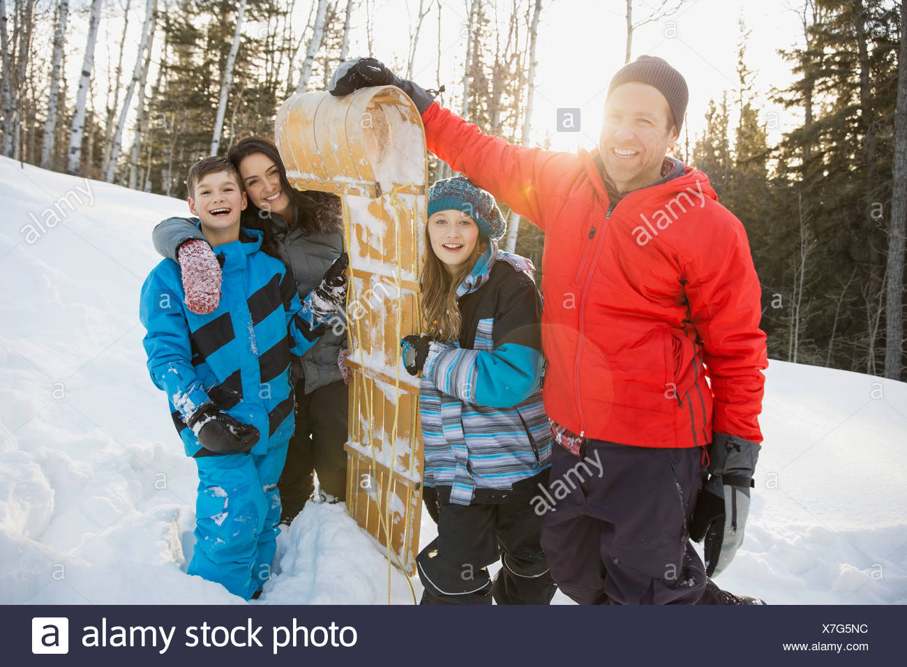 Portrait of family with toboggan in snow - Stock Image