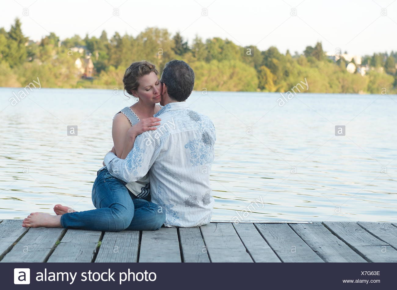Couple sitting on a wooden jetty embracing - Stock Image
