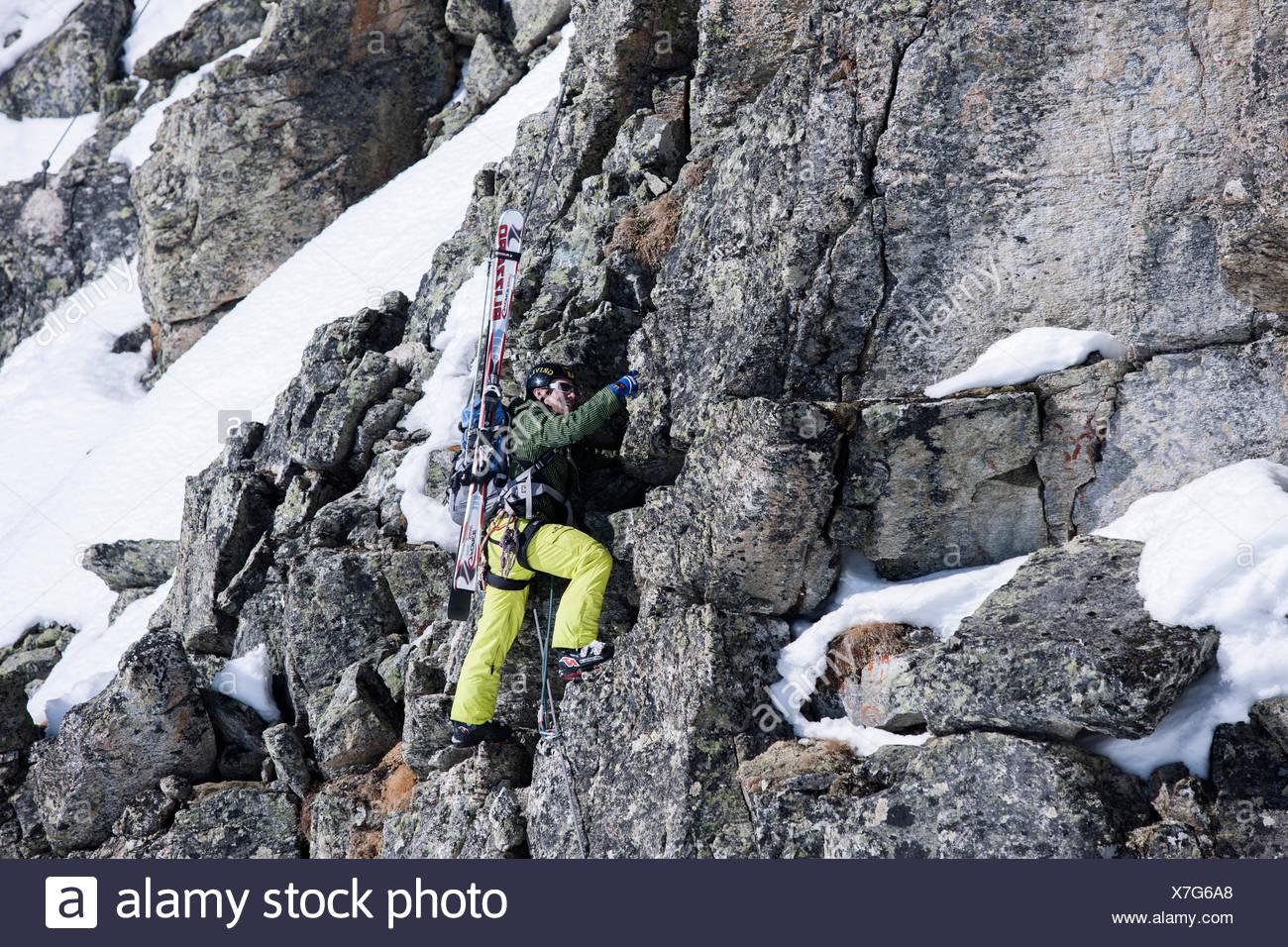 Freeride skier ascending the Winterklettersteig climbing route, Arlberg, Verwall Group, North Tyrol, Austria - Stock Image