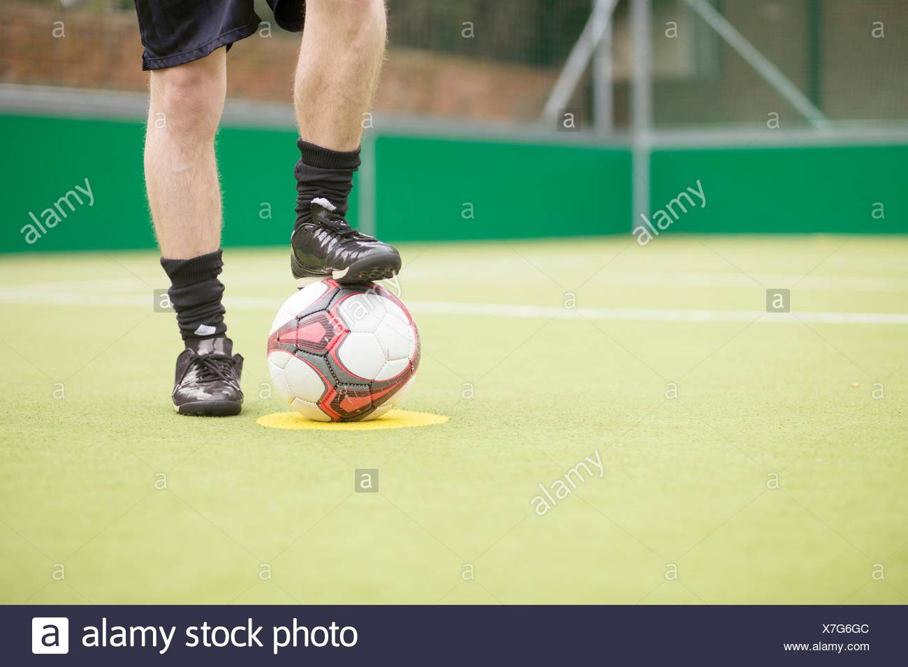 Young man on urban football pitch, foot on football, low section - Stock Image