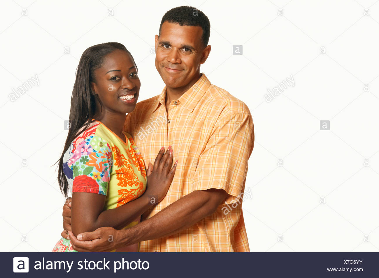 Portrait of a mature man embracing a mid adult woman and smiling - Stock Image