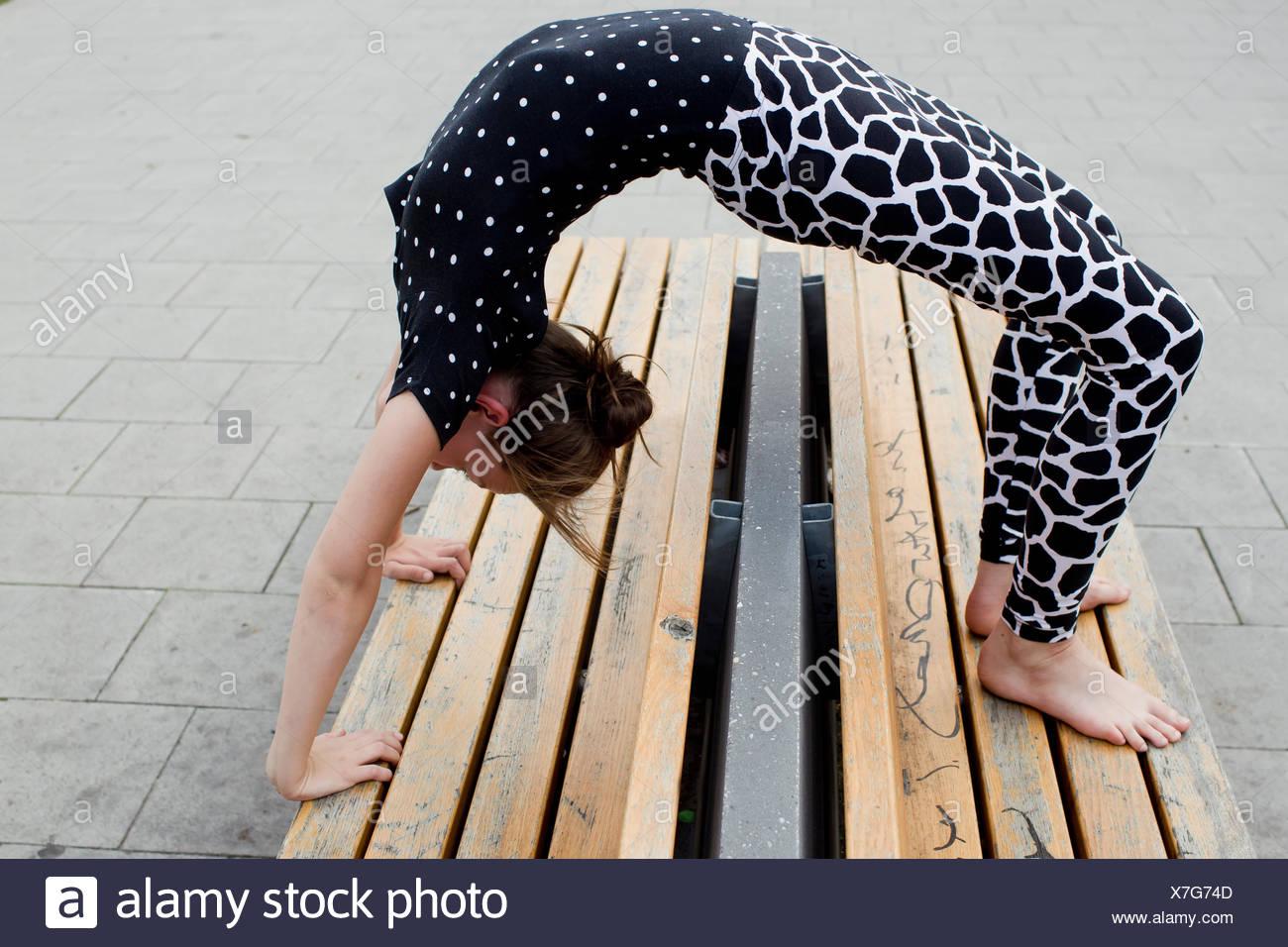 Teenage girl doing backwards bend on bench - Stock Image