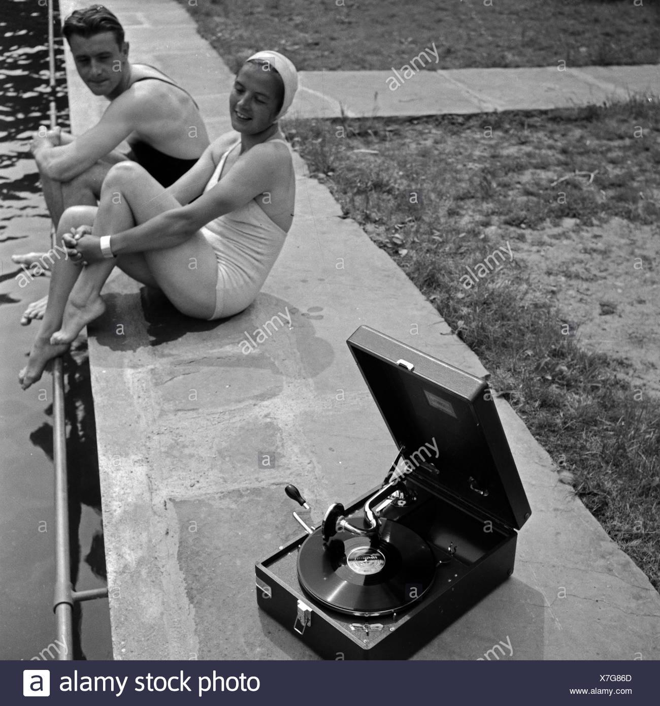 Ein junges Paar sitzt im Freibad am Beckenrand und hört die neuesten Schlager auf einem Elextrole Grammophon, Deutschland 1930er Jahre. A young couple sitting at the poolside and listening to the latest hits from an Electrola gramophone, Germany 1930s. - Stock Image