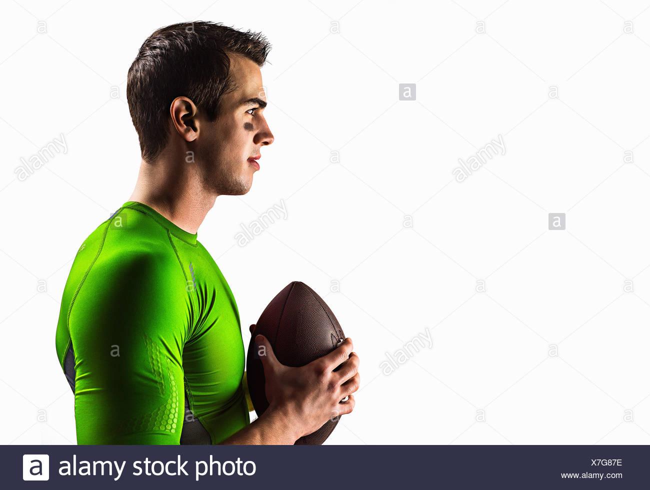 Athletic man holding football - Stock Image
