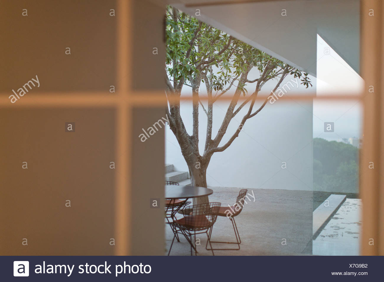 Table and chairs in courtyard - Stock Image