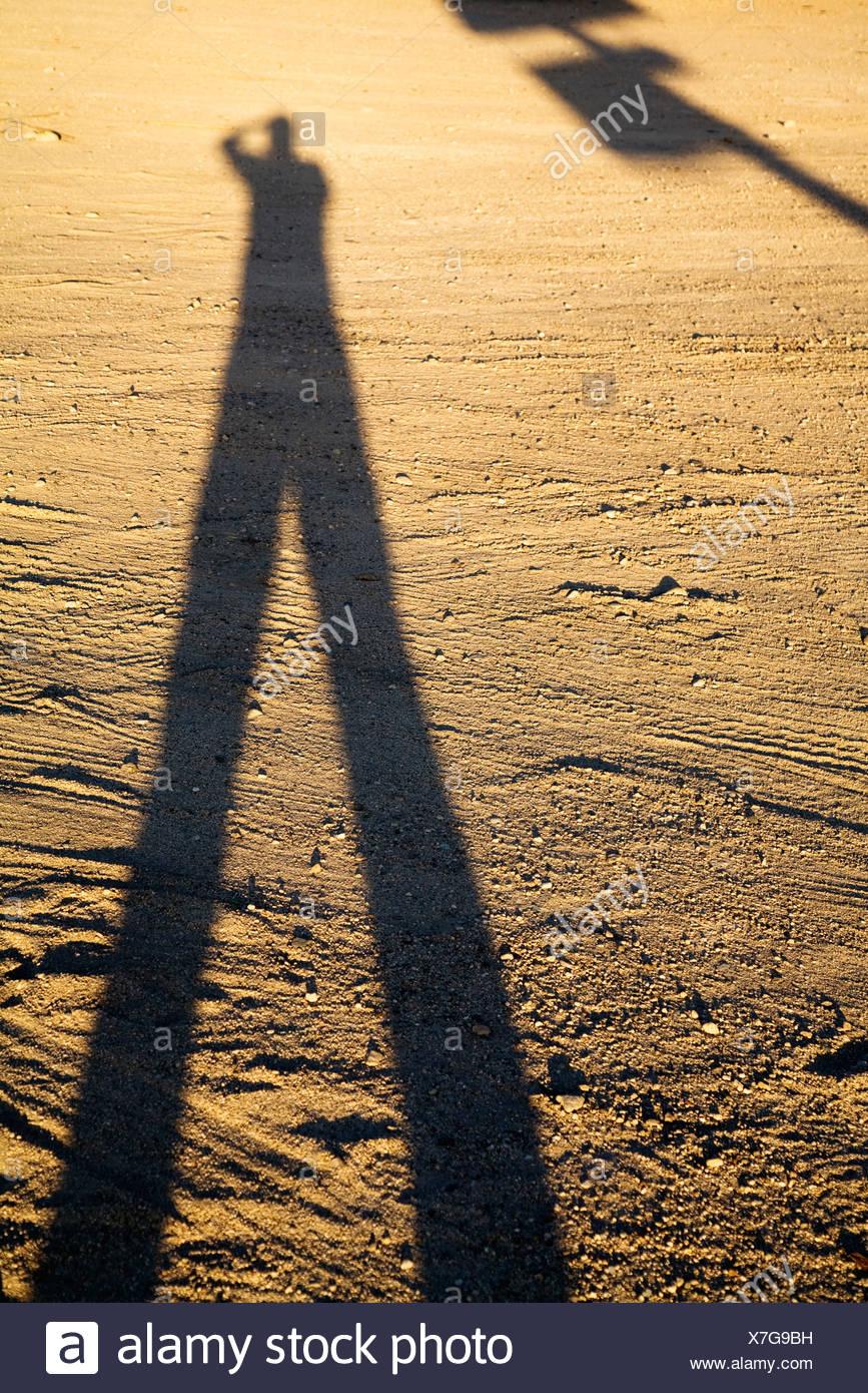 Shadow of man on dirt at sundown - Stock Image