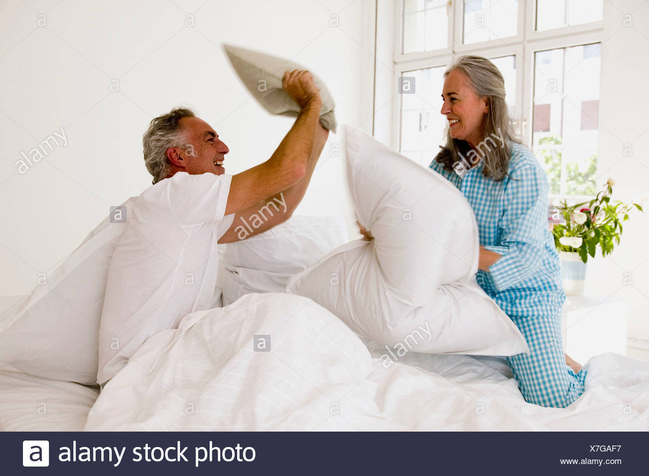 Mature A Letto.Mature Couple Having Pillow Fight On Bed Stock Photo 280027979