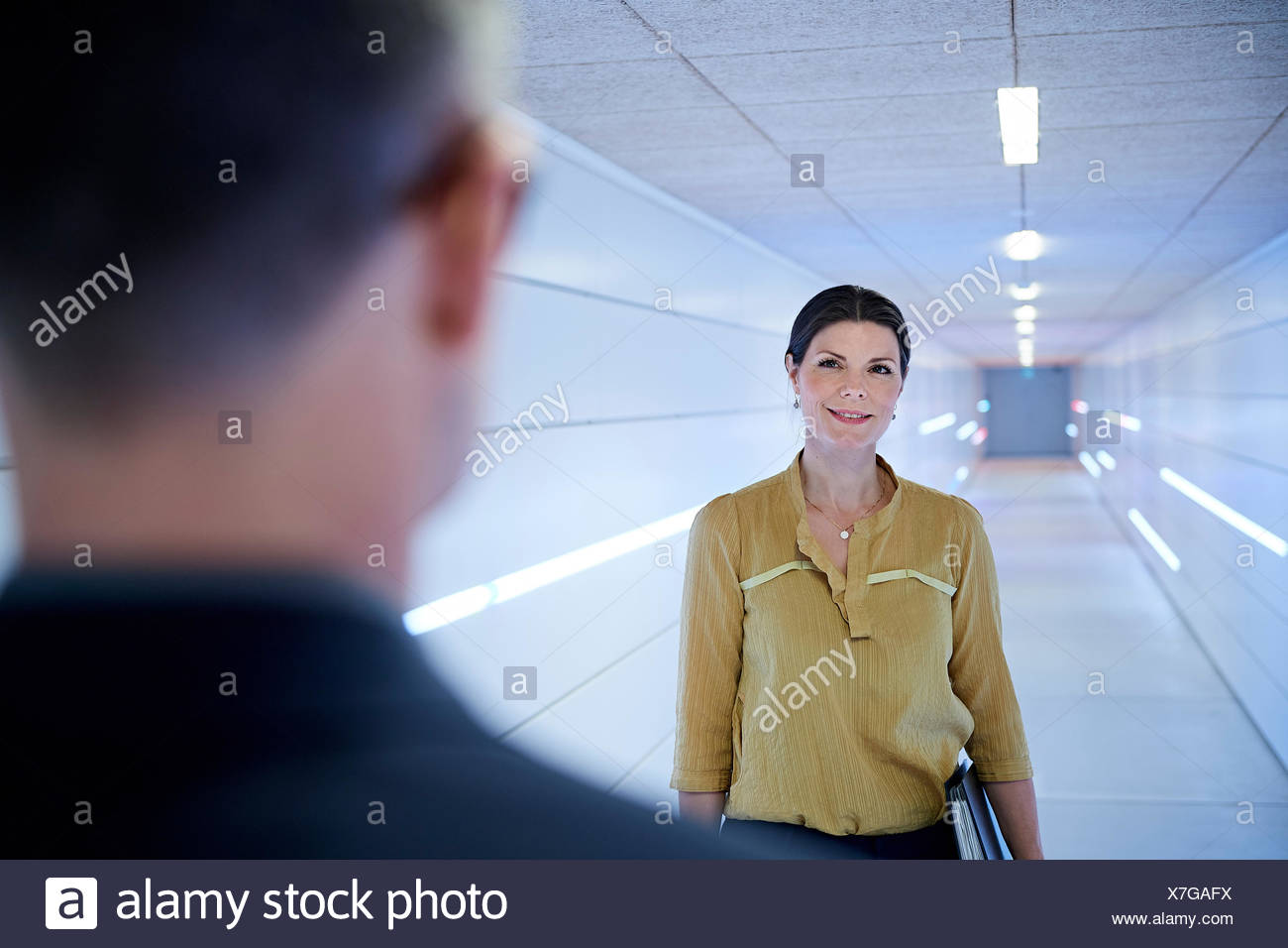 Over shoulder view of businesswoman approaching man in office corridor - Stock Image