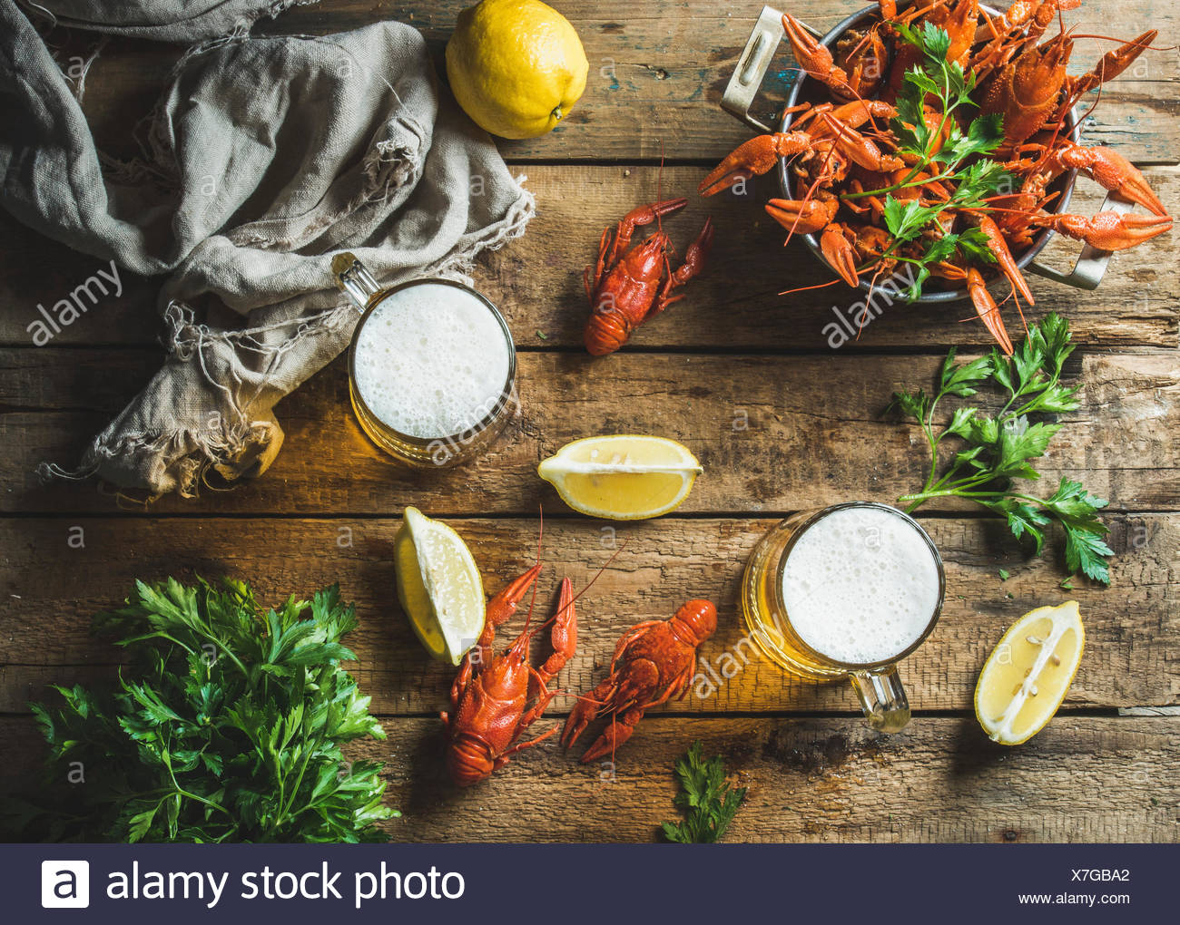 Two pints of wheat beer and boiled crayfish with lemon and parsley over old wooden rustic background, top view, horizontal compo - Stock Image