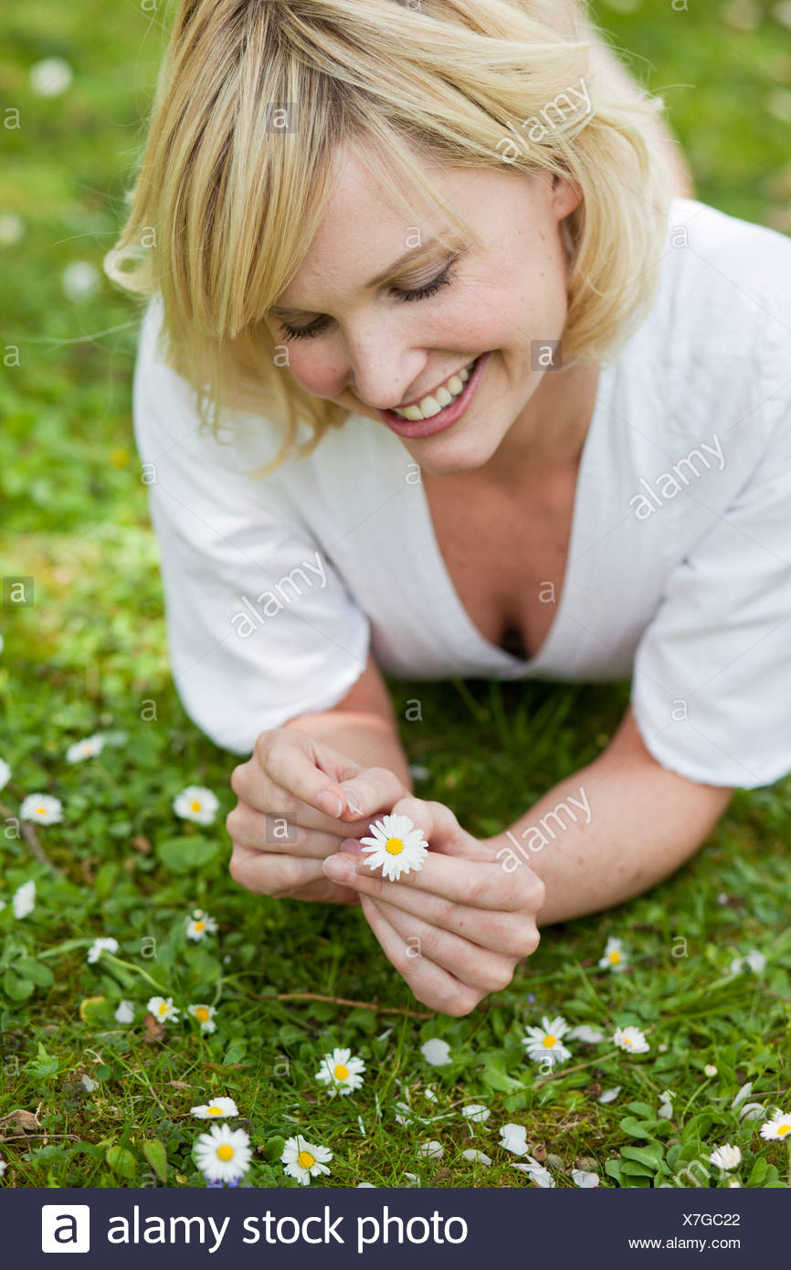 woman lying in garden with flower - Stock Image