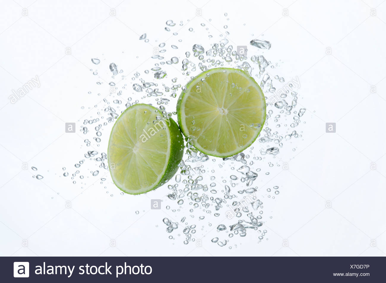 Lime halves submerged in sparkling water Stock Photo