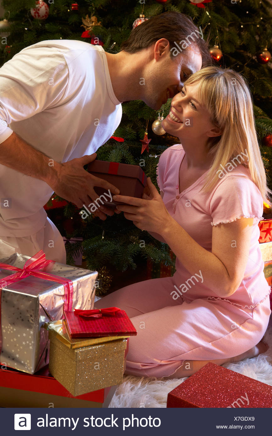 Couple Exchanging Presents In Front Of Tree - Stock Image