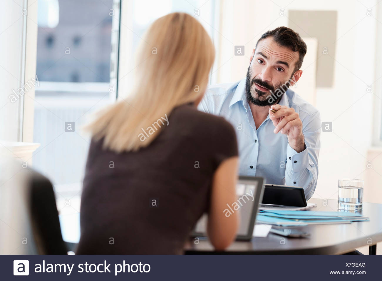 Man and woman talking in office Stock Photo