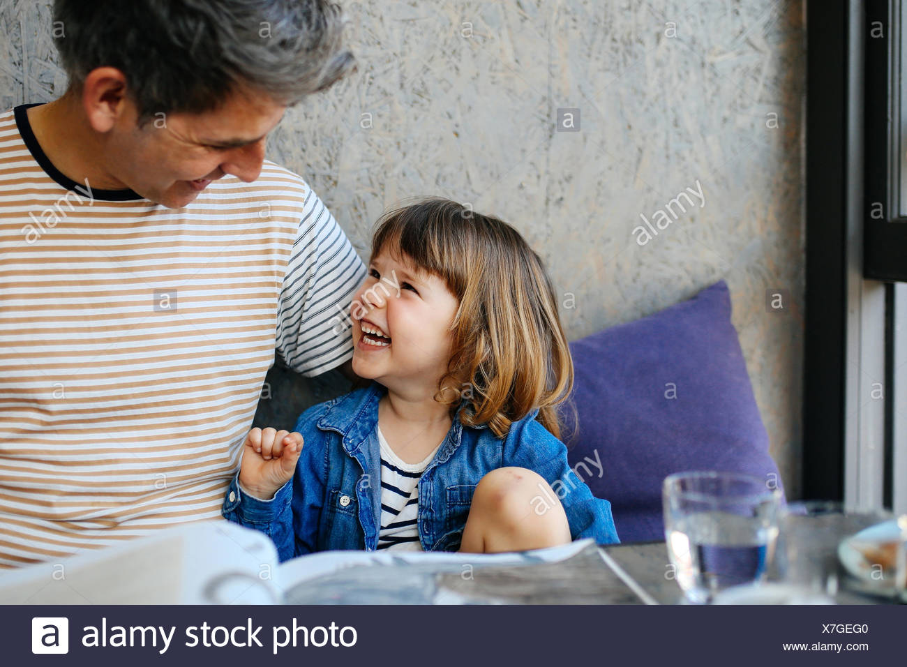 Girl laughing with father in cafe - Stock Image