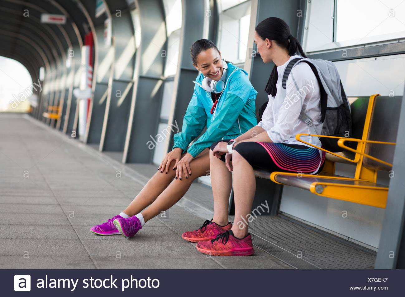 MODEL RELEASED. Two young women sitting on railway platform. - Stock Image