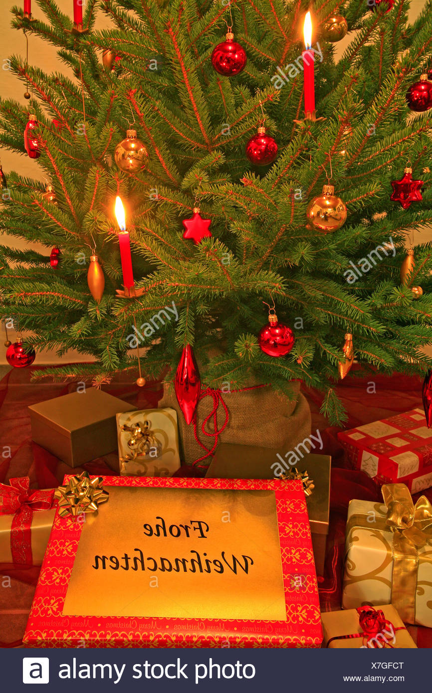 Decorated christmas tree with candles and porcelain ornaments, presents under the tree Stock Photo