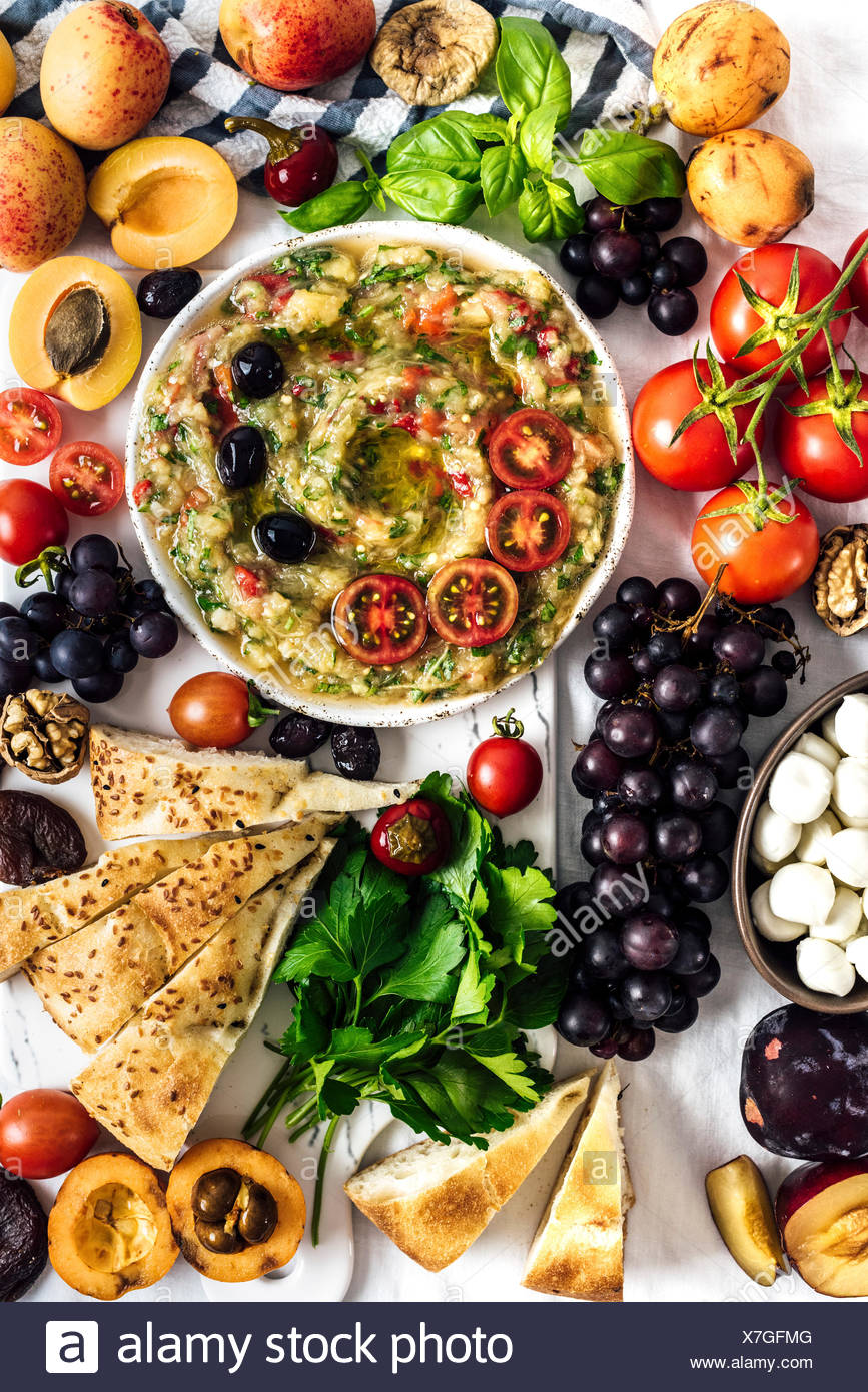 Eggplant babaganoush with red bell pepper and herbs on a snack board full of summer fruit photographed from top view. - Stock Image
