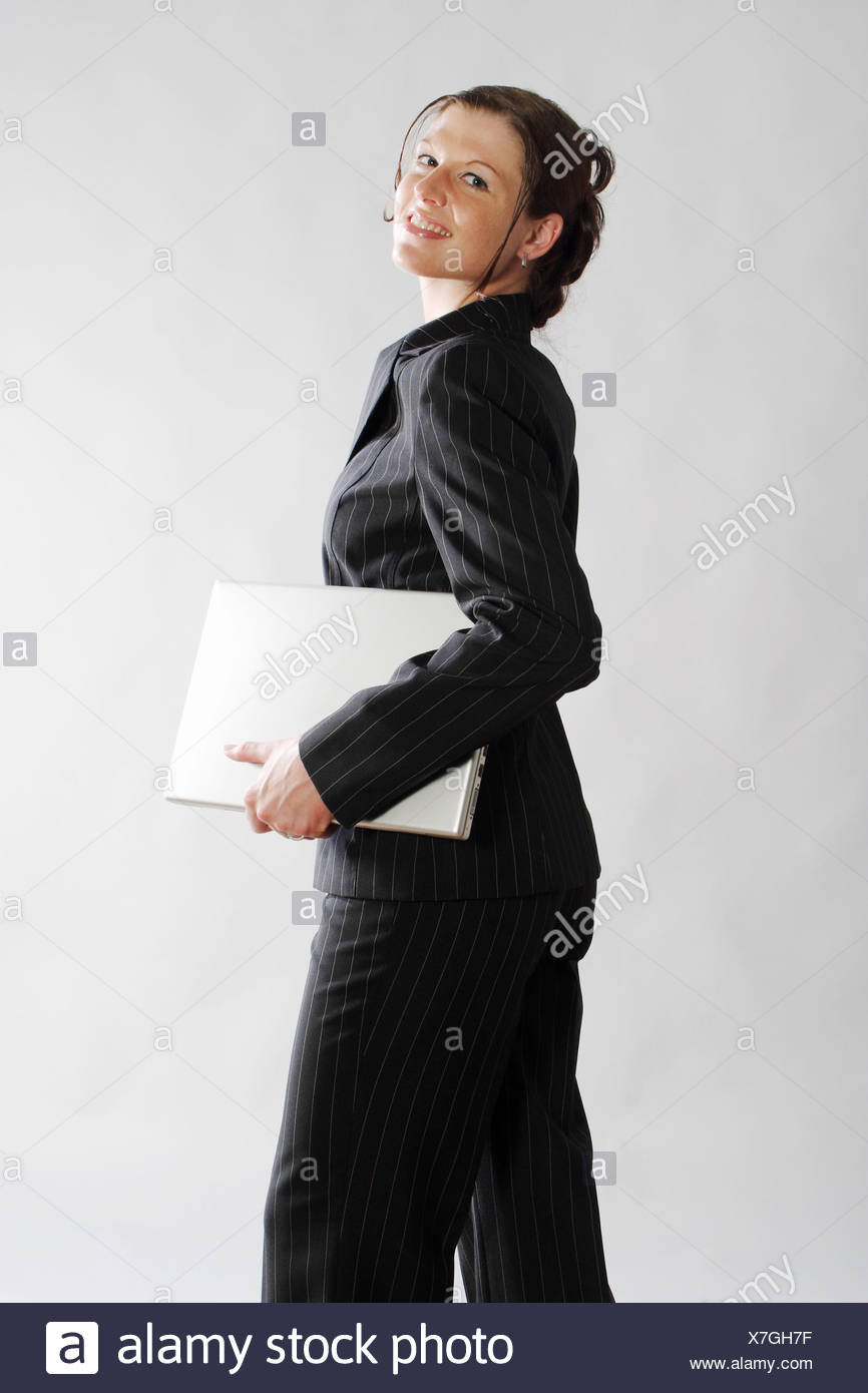 young woman in bussiness outfit with laptop under her arm, Germany - Stock Image