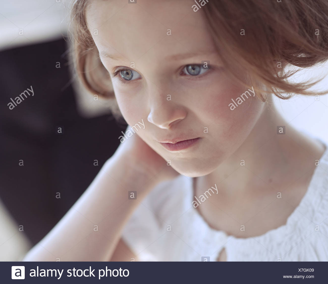 Close-up portrait of young girl looking away from camera - Stock Image