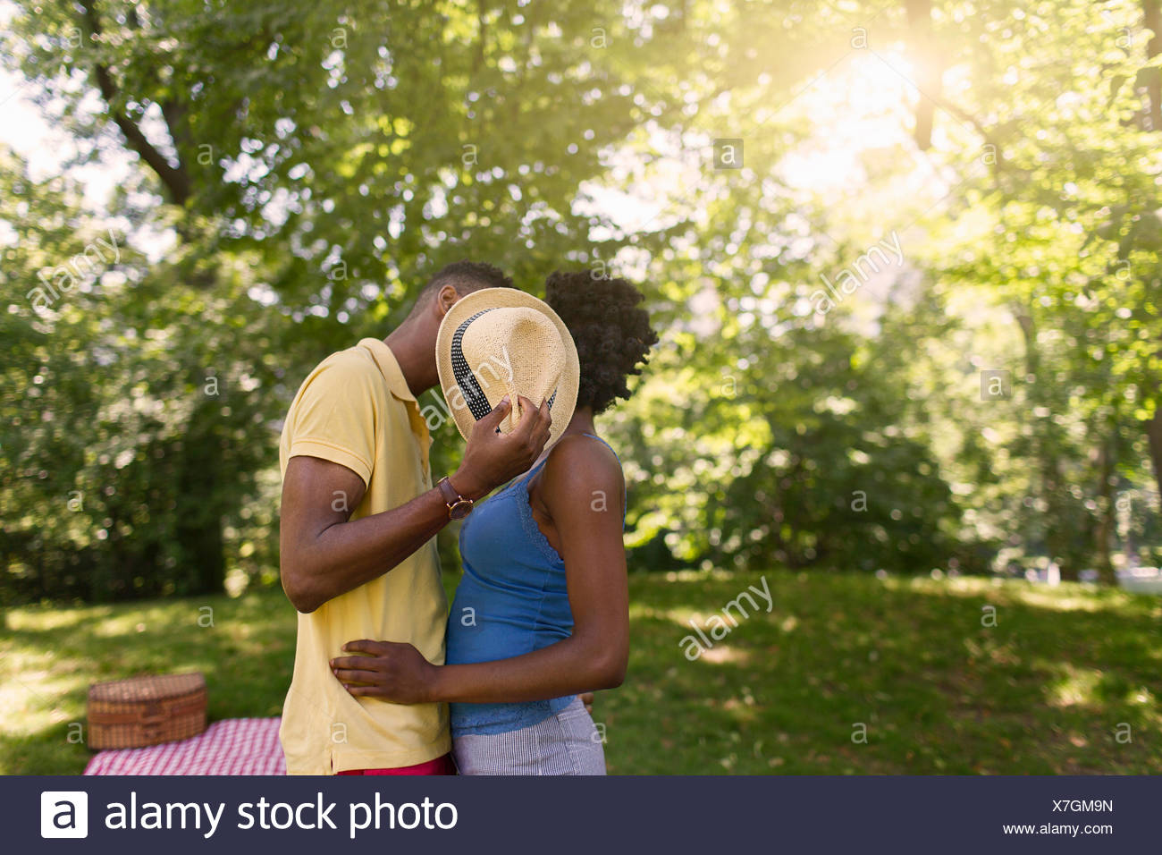 Young couple in park holding up hat to cover faces - Stock Image