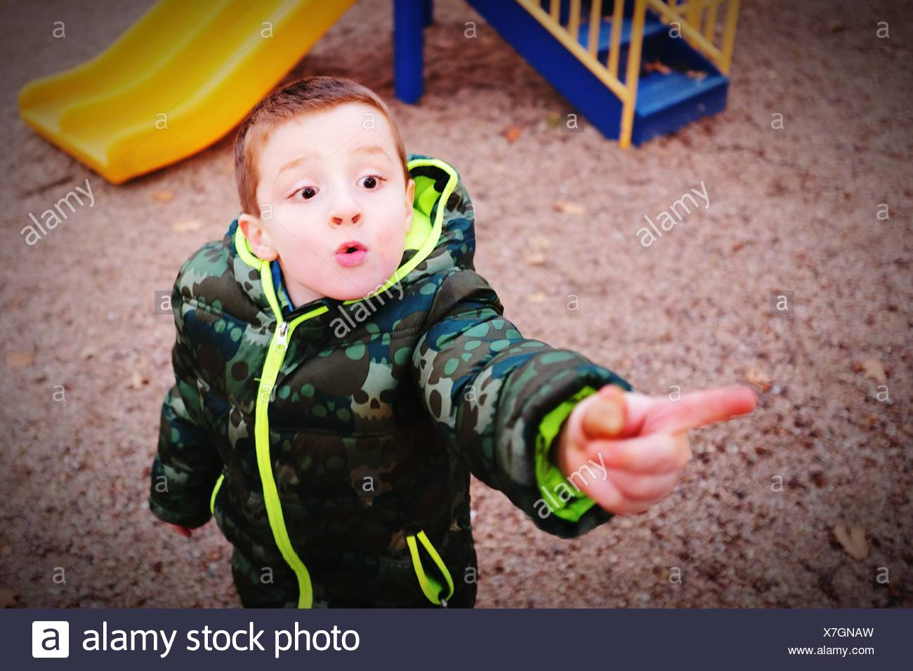High Angle View Of Boy Pointing Towards Something At Playground - Stock Image