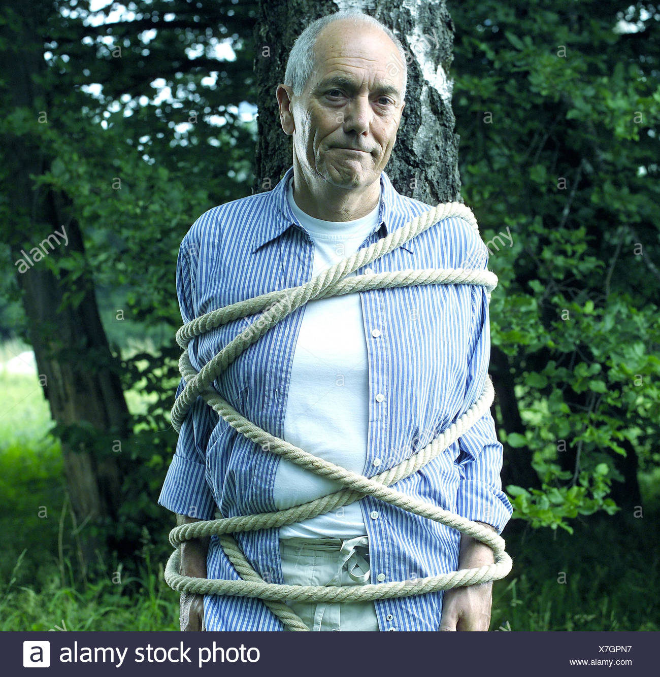 Garden, trunk, senior, tied up, half portrait, man, tree, bound, fastenedly, rope, cable, cord, helplessness, helplessly, defenceless, caught, trapped, hopelessness, hopelessly, maneuver, defenceless, powerless, defencelessness, powerlessness, expression - Stock Image