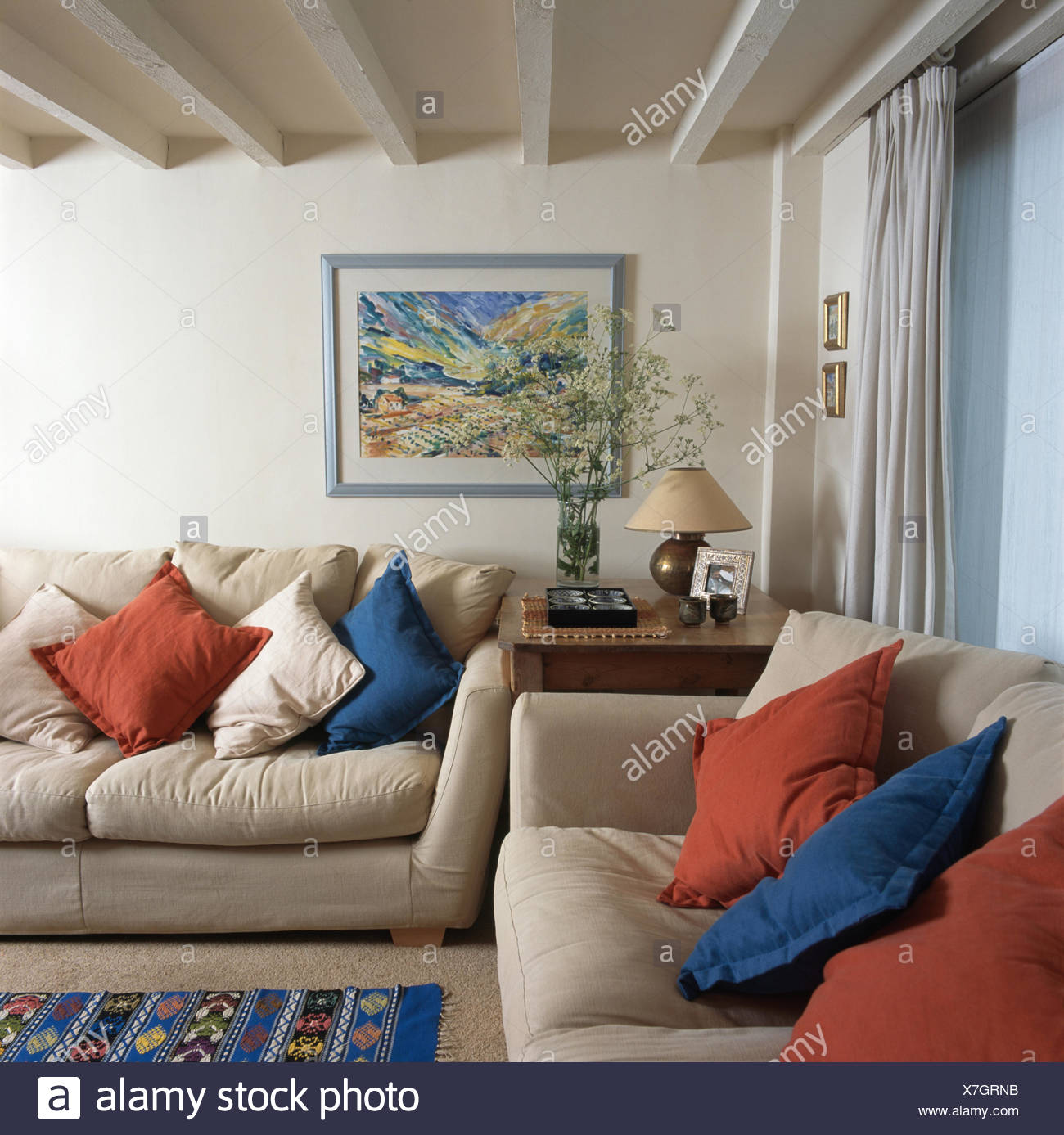Blue and red cushions on cream sofas in a traditional living room with a lime washed beamed ceiling - Stock Image