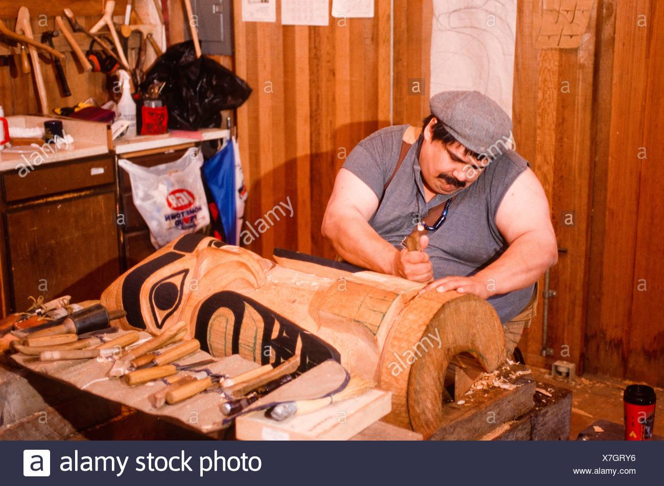 Tlingit carver J. Darald Dewitt at work on a totem at his Ketchikan workshop. - Stock Image