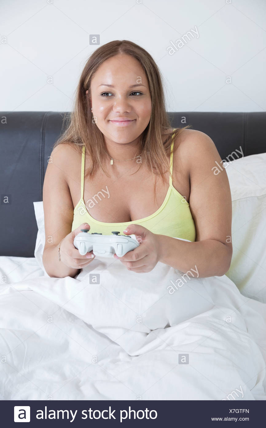 Young pregnant playing video game with remote control in bed - Stock Image