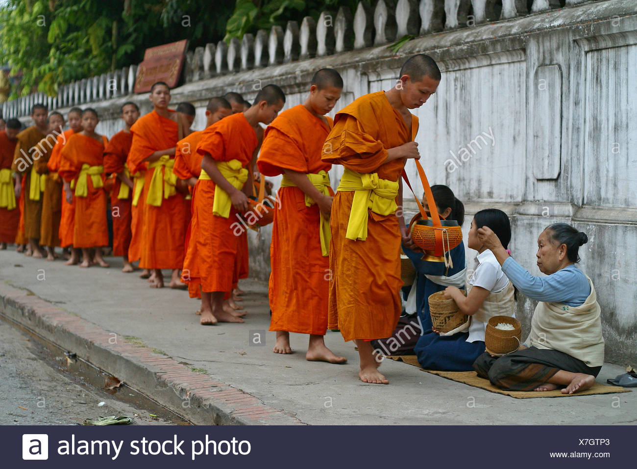 Monks and novices begging for their daily food in Luang Prabang, Laos - Stock Image