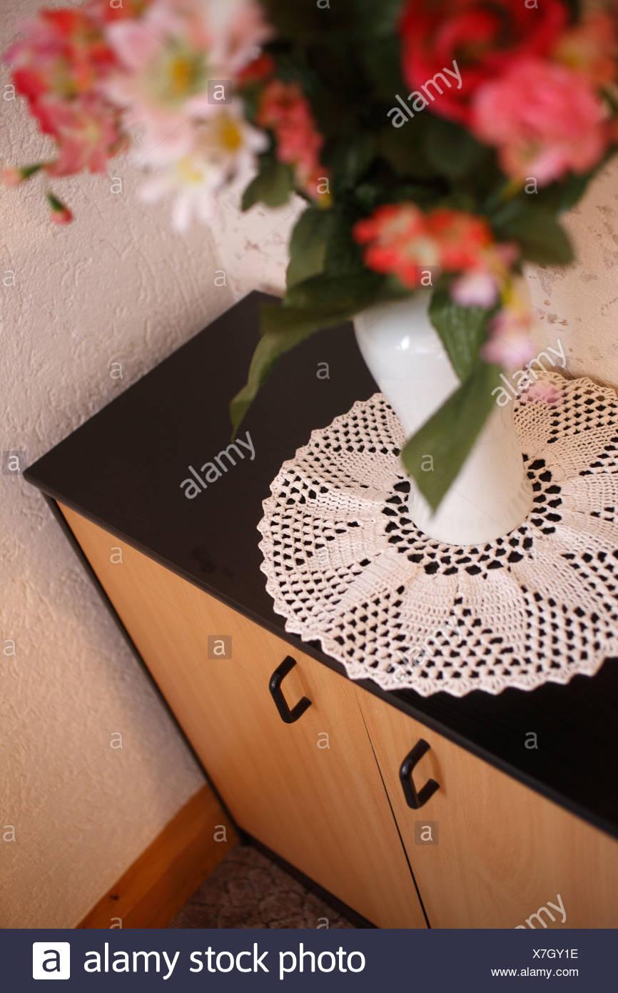 Schalkau, Germany, flower vase and crochet blanket on a cupboard - Stock Image