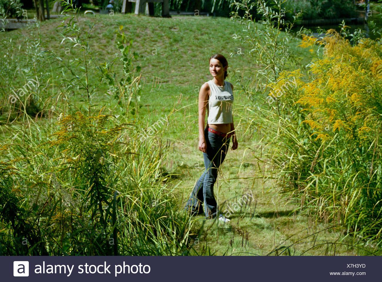 wait waiting park potsdam girlish arrive come meadow grass lawn green girl Stock Photo